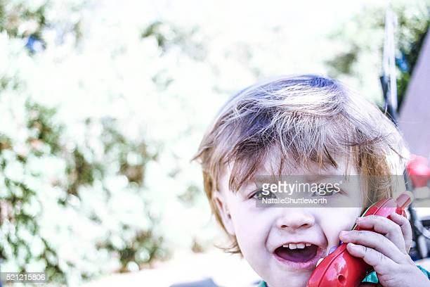 Toddler talking on a toy mobile phone
