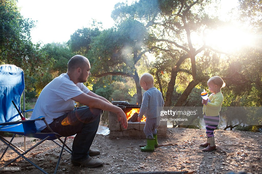 Toddler twins on camping site with father : Stock Photo