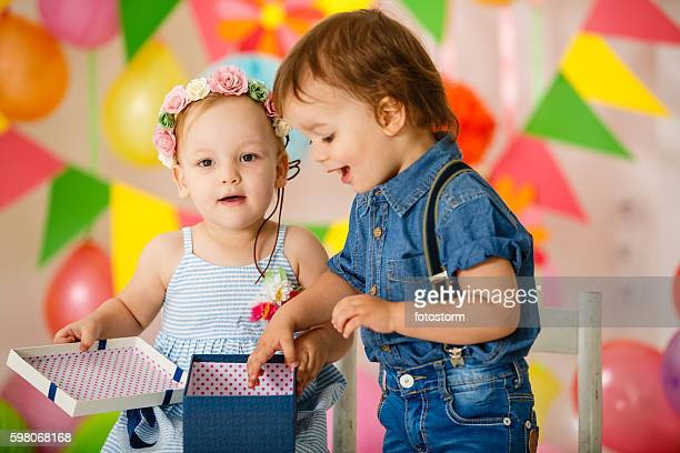 Toddler twins opening present at birthday party