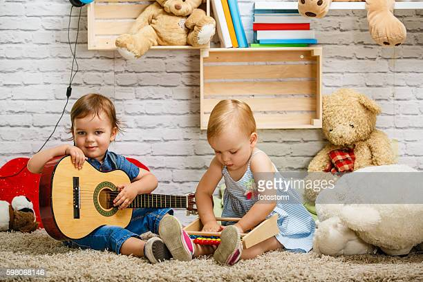 Toddler twins playing together at home