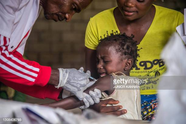Toddler undergoes a measles vaccination at a centre in Temba, near Seke Banza, western DR Congo on March 3, 2020. - Seventy-three thousand children...
