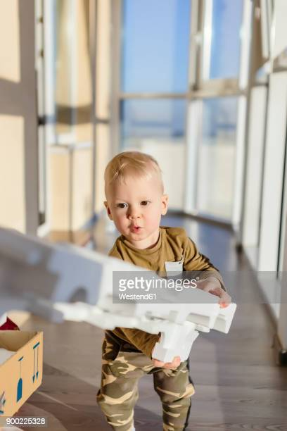 Toddler unpacking cardboard box