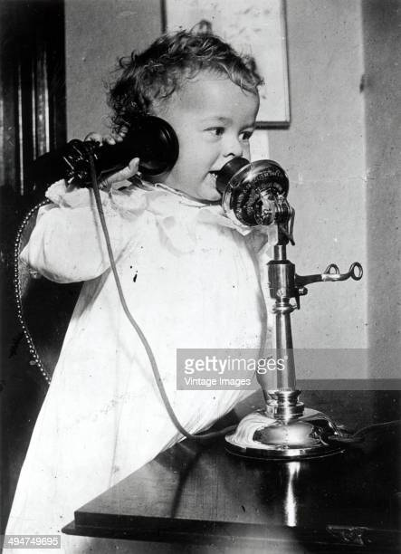 A toddler using a candlestick telephone circa 1940