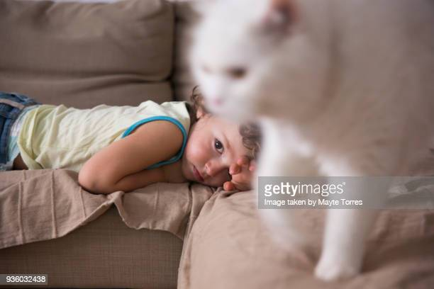 Toddler waking up on sofa and cat