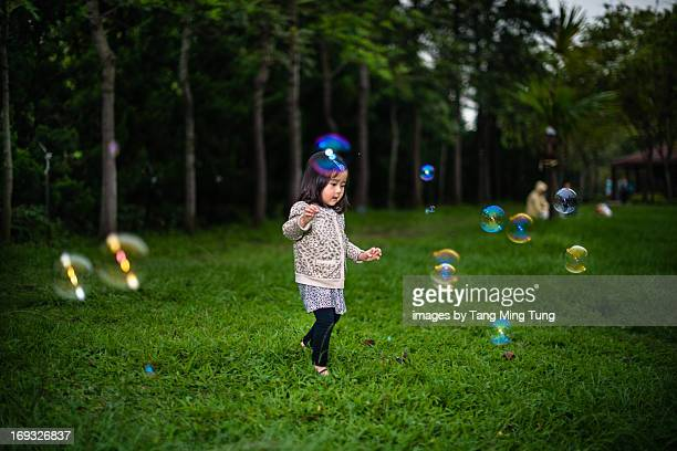 Toddler walking on the lawn surrounded by bubbles