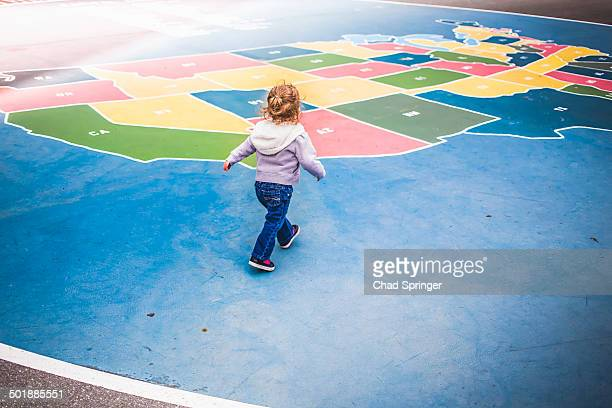 Toddler walking over map of USA in playground