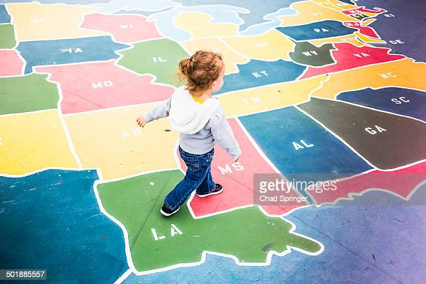 toddler walking over map of usa in playground - us map stock photos and pictures