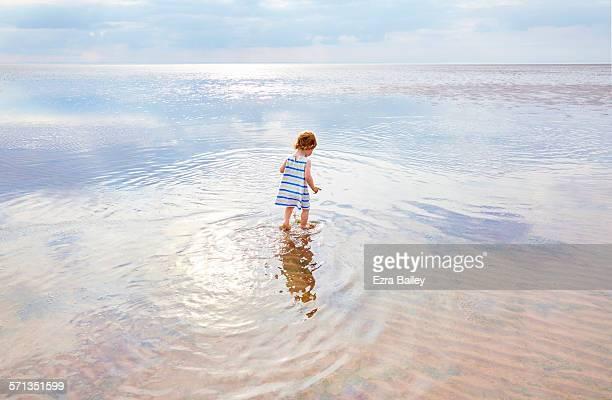 Toddler walking through shallow water at lowed