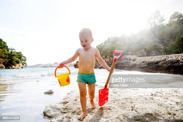 Toddler walking with bucket and shovel at the beach