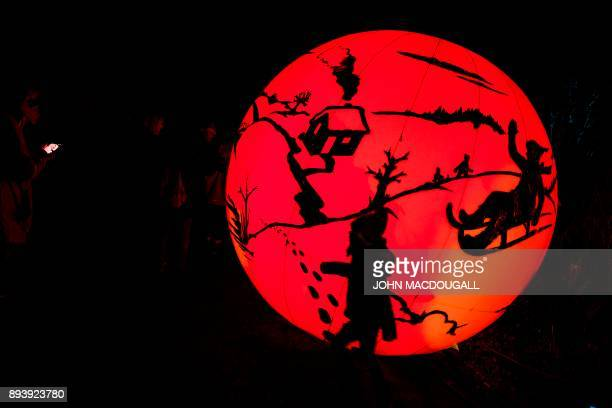 A toddler walks in front of a giant illuminated sphere at the Christmas Garden light show in Berlin's botanical garden on December 16 2017 The show...