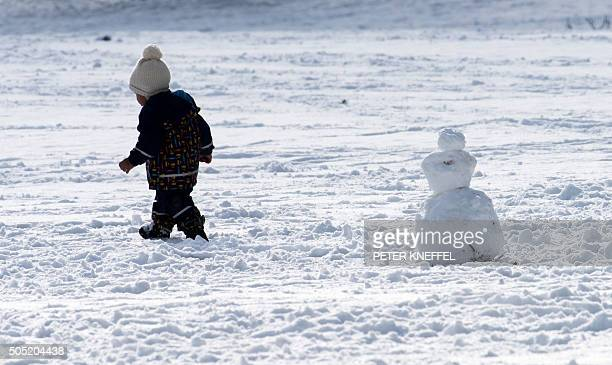 A toddler walks past a snowman at the Englischer Garten park in Munich southern Germany on January 16 2016 / AFP / dpa / Peter Kneffel / Germany OUT