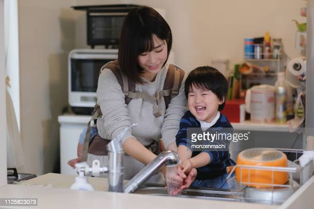 toddler washing hands with mother at kitchen - homemaker stock pictures, royalty-free photos & images