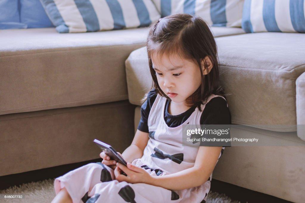 Toddler watching a cartoon smartphone screen : Stock Photo
