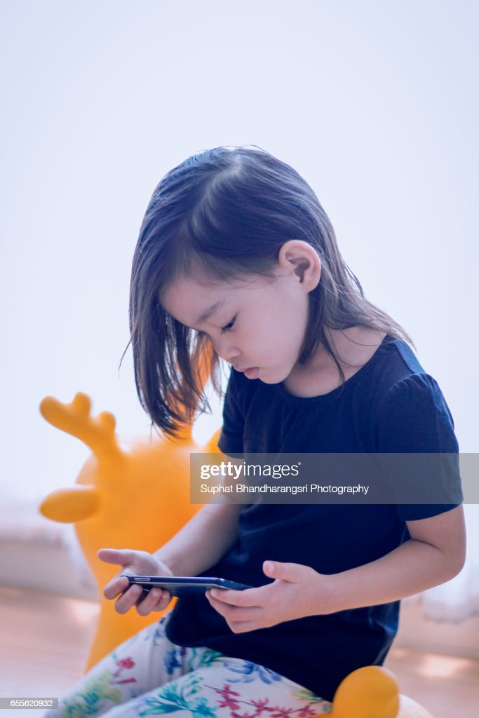 Toddler watching a video clip on yellow deer toy : Stock Photo