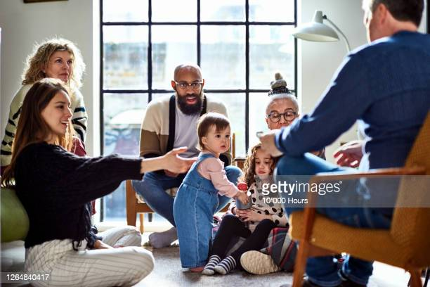 toddler watching adults in living room - multi ethnic group stock pictures, royalty-free photos & images