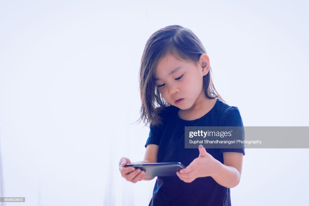 Toddler watching cartoon near window : Stock Photo