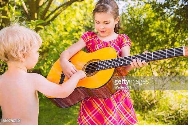 Toddler watching girl playing guitar in garden