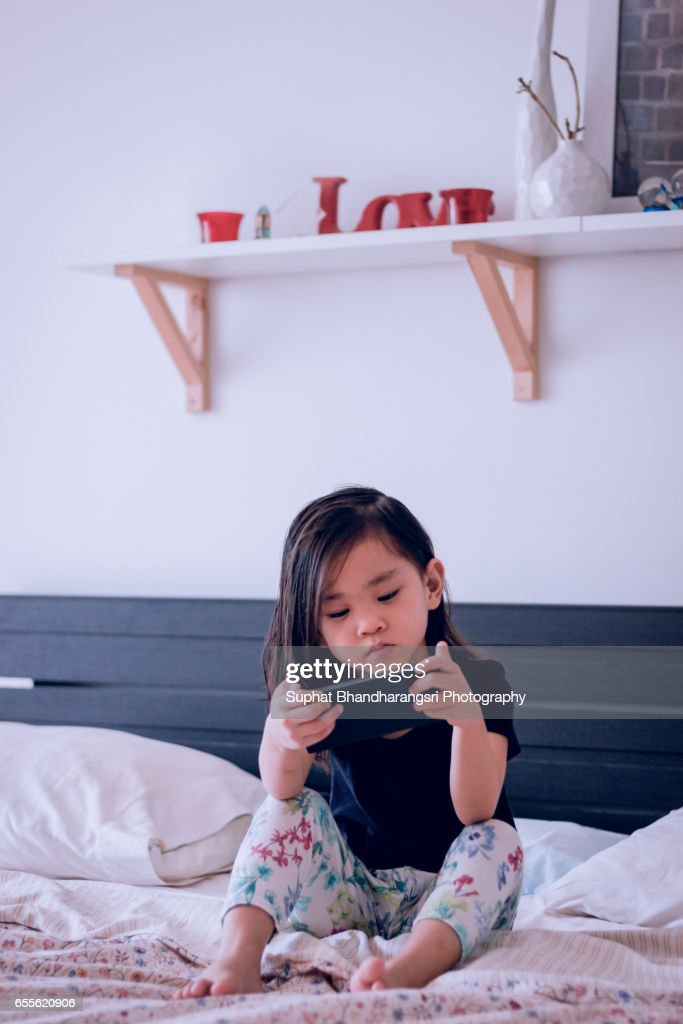 Toddler watching smartphone on the bed : Stock Photo