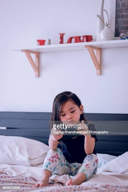 Toddler watching smartphone on the bed