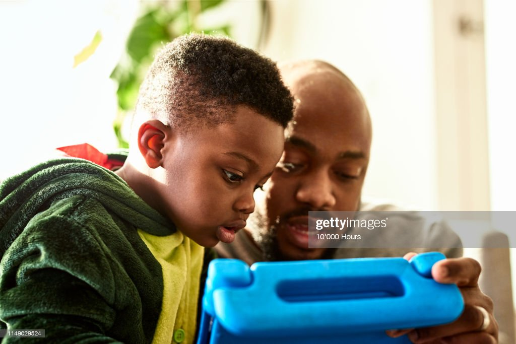 Toddler watching tablet with father : Stock Photo