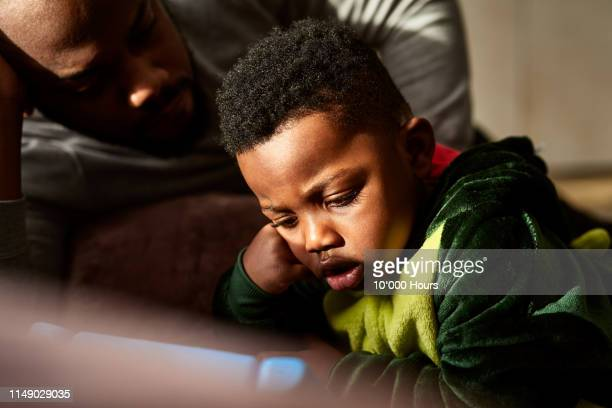 toddler watching tablet with open mouth - black stock pictures, royalty-free photos & images