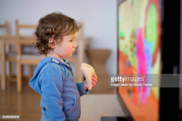 toddler watching tv with a sandwich - fernsehserie stock-fotos und bilder