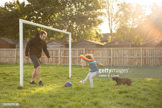 a toddler wearing a colourful top kicks a football towards her uncle on goals as her dog chases her - season 3 stock pictures, royalty-free photos & images