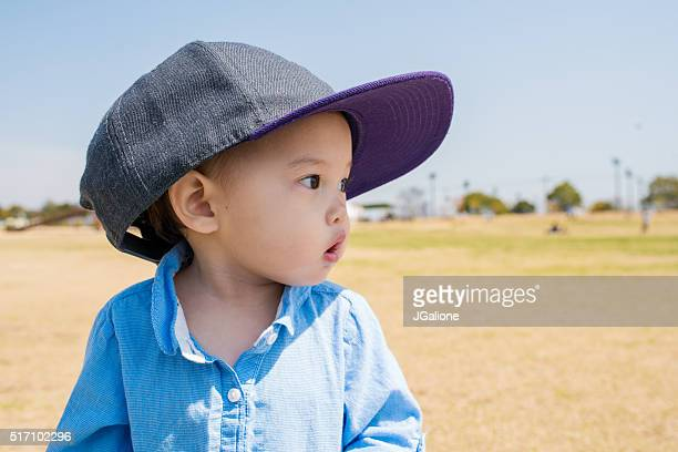 Toddler wearing an adult sized baseball cap