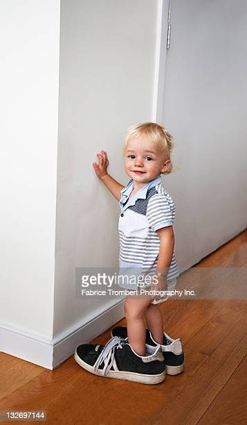 Toddler wearing dad's sneakers