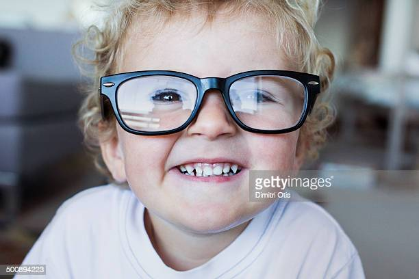 Toddler wearing his dad's reading glasses