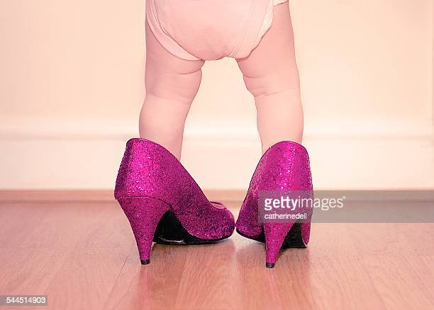 Toddler wearing mother's shoes