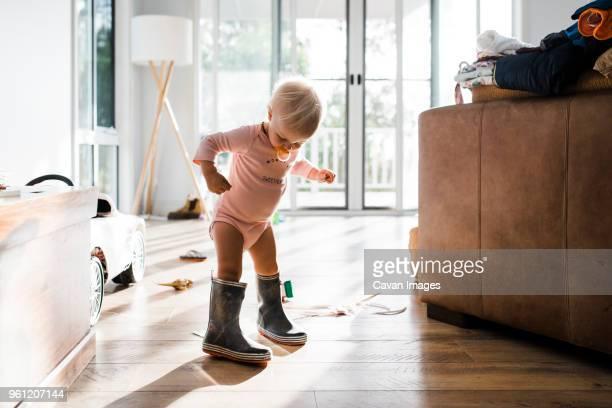 toddler wearing rubber boots while sucking pacifier at home - surdimensionné photos et images de collection