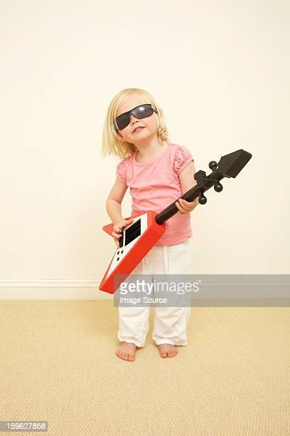 Toddler wearing sunglasses, playing guitar