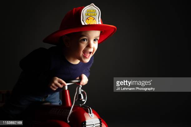 toddler wears a play firefighter helmet in a studio shot and is laughing - firefighter's helmet stock photos and pictures