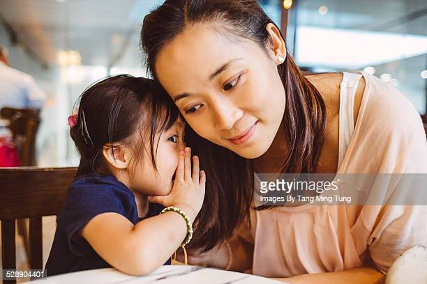 Toddler whispering into mom's ear in cafe