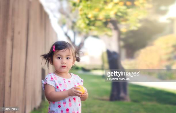 Toddler With An Orange Found Outdoors