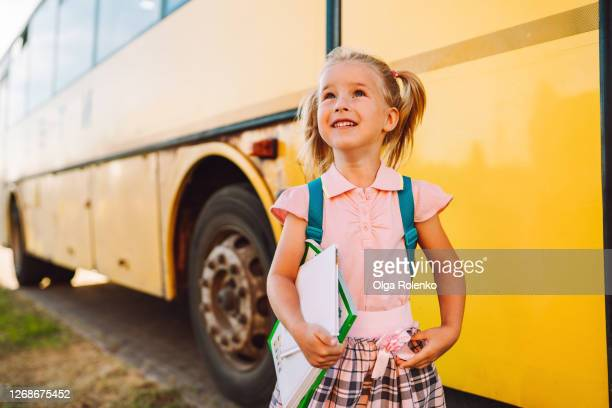 toddler with books beside school bus - first day of school stock pictures, royalty-free photos & images