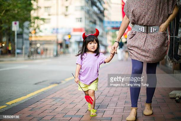 Toddler with devil accessories strolling with mom