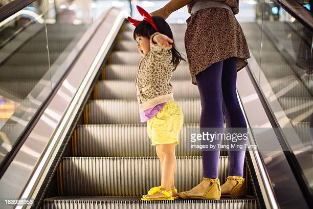 Toddler with devil headband on escalator with mom