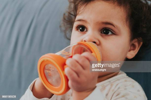 toddler with her baby bottle - onebluelight stock pictures, royalty-free photos & images