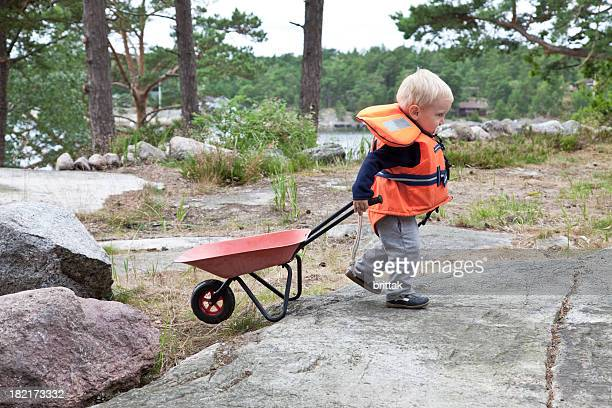 Toddler with life west and wheelbarrow