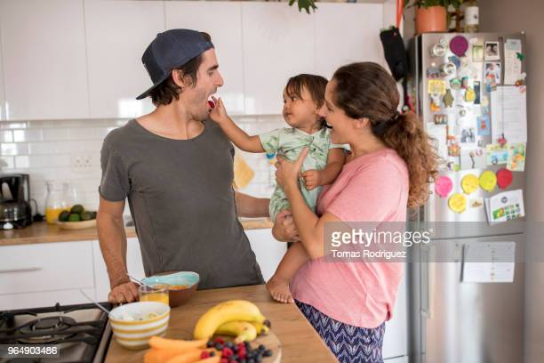 Toddler with mum in kitchen feeding dad with fruit