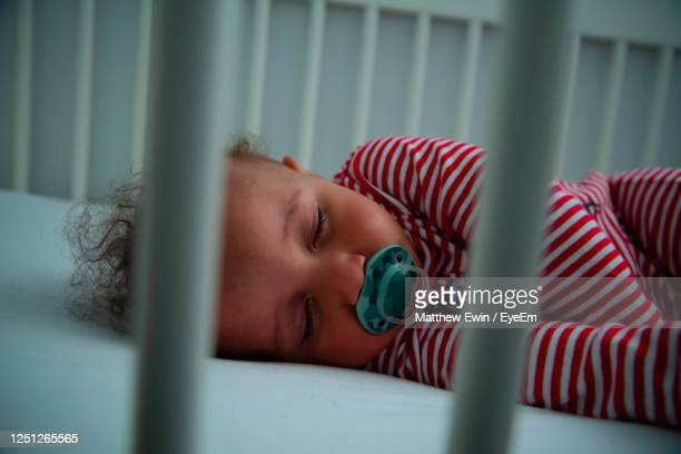 toddler with pacifier sleeping on bed - one baby boy only stock pictures, royalty-free photos & images