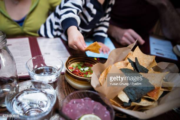 Toddler With Parents Having Food At Table