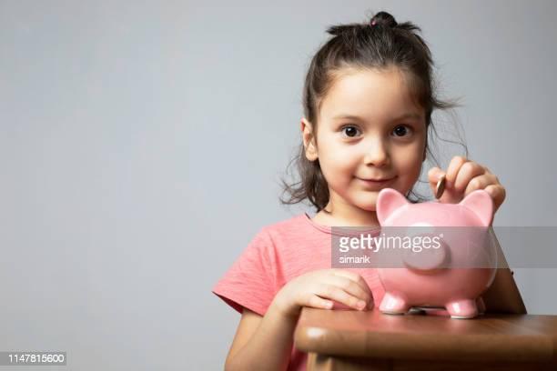 kleinkind mit schweinebank - sparschwein stock-fotos und bilder