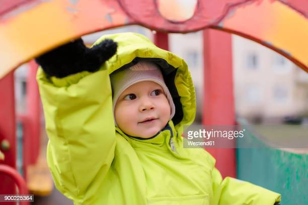 Toddler with rain jacket on playground