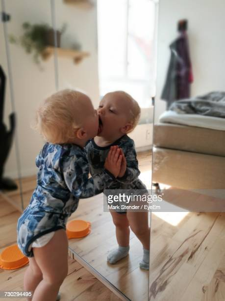 Toddler With Reflection Kissing On Mirror At Home