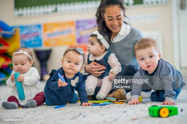 toddlers with their caretaker - preschool stock pictures, royalty-free photos & images