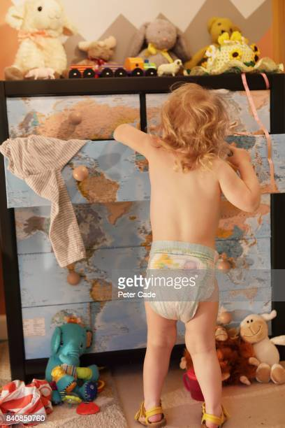 Toddller looking in chest of drawers in bedroom