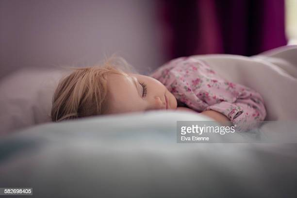 Todler girl (2-3) sleeping on bed